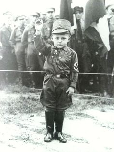 A young boy wearing an SA uniform - Berlin c.1934....herd mentality is sad anywhere