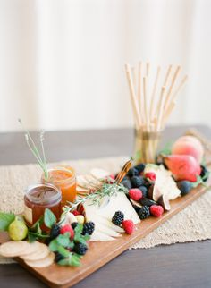 Pretty cheeseboard with cheeses, breadsticks, figs, preserves, berries and crackers.