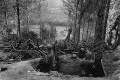 Two GI's inspect a German machine gun position - around the tunneled outpost are 2 MG42's, field radio and telephone, rifles, helmets, ammunition, and multiple grenades