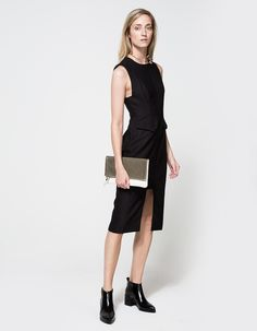 From Finders Keepers, a mid weight fitted dress with symmetric cut in black. Features high rounded neckline, wide tank straps, structured top, front waist flaps on faux pockets, rectangular front cutout, long zipper back and fully lined.  •Mid weight f