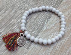 Armband van 6mm witte houten kralen met een donker multi color kwastje en metalen Arabisch geluksmuntje. Te koop bij JuudsBoetiek voor €3,50. Bestellen kan via juudsboetiek@gmail.com