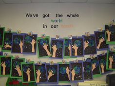 """We got the whole world in our hands:""  These art projects were created by Grade 1 students and they traced their hands, painted a picture of the Earth, and added confetti stars."