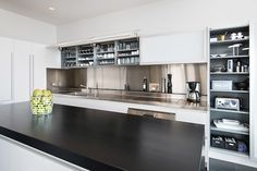 Sleek black and white kitchen features modern white cabinets paired with oversizes cabinet pulls alongside a stainless steel backsplash alongside an integrated sink and induction cooktop below a stainless steel backsplash with narrow ledge used as spice shelf.