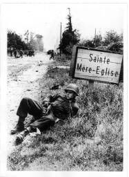 Elmer Habbs, Delaware, relaxes … Further up the road, more American troops engage in mopping up operations Sainte Mere eglise on the Cherbourg peninsula … = [Sur le bord d'une route, à côté d'un panneau de signalisation, le soldat Elmer Habbs se repose].