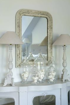 White console table with dual white lamps and various sized candy jars filled with white seashells. Beach style shabby chic.