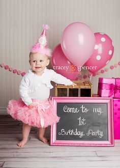 Photograph of a one-year-old inviting everyone to her 1st birthday party. See more first girl birthday party ideas at www.one-stop-party-ideas.com
