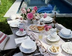 Outdoor tea table with vintage linen runner and assorted china and porcelain