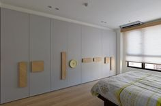 oversized wood panels are used instead of regular handles,  creating visual points in the room, as well as places to hang clothes.  http://design-milk.com/taiwanese-apartment-showcasing-toys-travel-souvenirs/