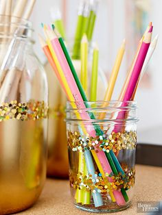Sparkling storage jars brighten up any desktop space. To make, mask a portion with painter's tape and cover the open area with frosted-glass spray paint (which acts as a primer). When dry, add a coat of gold spray paint. Apply double-sided tape and coat with glitter.