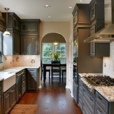 dark gray cabinetry, farmers sink, arch to dining room.