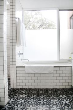 love the dark grout on the white tiles, the patterned floor and the big a## window