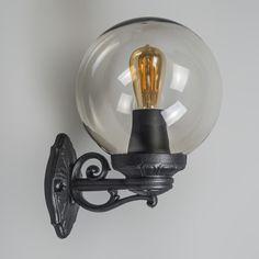 Aplique BASSO negro Preciosa lámpara con detalles ornamentales en plástico. Esta lámpara se completa con una esfera transparente, a través de la cual se ve la bombilla. Los materiales son de alta calidad y resistentes a la intemperie y a los impactos. La fuente de luz es de casquillo E27 y funciona con varias tipos de luz (halógena, bajo consumo y LED).