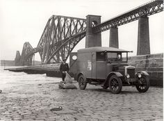 Royal Mail van with postman unloading bags on the jetty