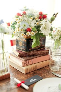 vintage tin with flowers inside placed on a stack of books. I like the pop of blue and red with the white and yellow.