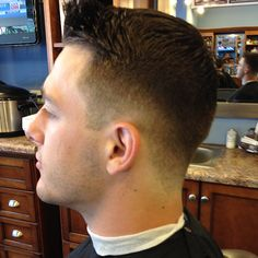 Fade haircut with a short pompadour.