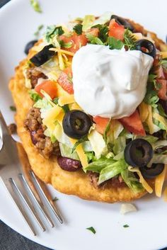 An image of Native American Tacos made with Navajo fry bread then topped with taco meat beans lettuce tomatoes cheese olives and sour cream. Indian Taco Recipes, Mexican Food Recipes, Beef Recipes, Dinner Recipes, Cooking Recipes, Recipies, German Recipes, Navajo Tacos, Native American Fry Bread