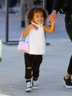 Fashion forward: The little girl was head-to-toe cuteness in a white turtleneck sweater, distressed denim trousers and sporty Converse trainers