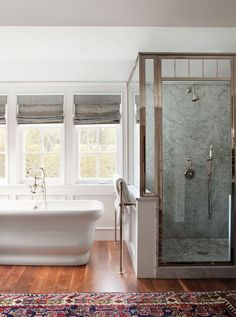 A nickel shower and stand-alone bathtub. Love the rug in the bathroom. #bathroom #interiors