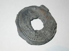 Cloth seal from Leiden in the Netherlands. It is stamped with the word 'Leyden' in black letter on both sides. Lead seals were attached to bales of cloth for quality control. They provide details about the fabric: brand name, size and source, as well as the maker's personal mark. This seal was attached to linens or cottons imported from Europe and indicates the important role London played in the international textile trade.  Production Date: Late Medieval; 15th century
