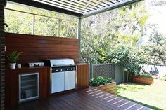 Outdoor built in BBQ and fridge. Trellis design hanging on fence and wooden planter boxes and outdoor seating. The Block All Stars: Phil and Amity's House