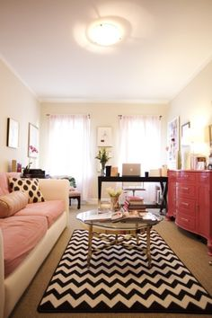Narrow rooms can be glam. Chevron rug, painted dresser, glass coffee table, natural light galore.