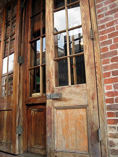 I love the aged wood, the rustic look, and the windows in these doors.  It looks great up against the brick.