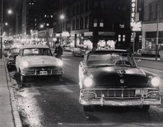 Duluth police patrolman Donald Rockwell checks a driver's license as patrolman Edward McLean pulls the squad car to the curb on Superior Street near 5th Avenue West. (Earl Johnson / News-Tribune) 1957