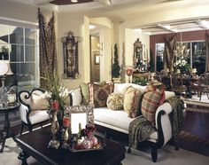 This lavish room is bursting with a variety of textures and tones, from dark wood coffee table and sofa frame, to brick patterns in hardwood floor, to gold drapes and tapestries over beige walls.
