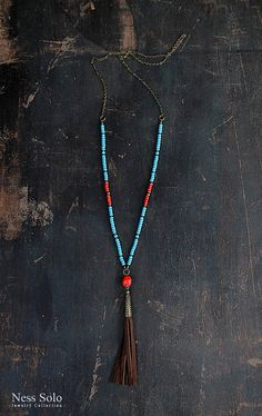 Long beaded boho necklace with mat blue and coral red glass beads, a coral pendant and a genuine leather tassel.  The necklace measures 92 cm (36 1/4