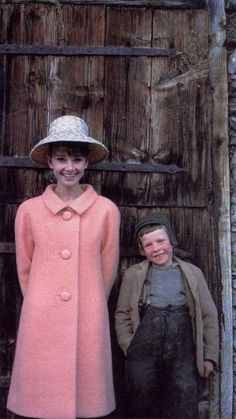 The actress Audrey Hepburn photographed with a little boy by Howell Conant to a fashion editorial (for the American LIFE Magazine, edition of May 1962, unpublished photo) at a farm near her house in the Swiss Alps, in February 1962.  Audrey was wearing:  Coat: Givenchy (of pink pale wool, of his collection for the Spring of 1962). Hat: Givenchy (of straw, of his collection for the Spring of 1962). Audrey's hairstyle was done by Alexandre de Paris and her makeup by Leo of Helena Rubinstein.