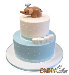 Birdie On Elephant Baby Shower Cake  This stunning cake was ordered for the occasion of the Baptism of little Luke. Although the theme was for a baby, the brief was not to have balloons or baby stuff cluttering up the cake, but rather to keep it simple in keeping with the religious occasion that it was.  We designed a two tier cake in baby blue and white fondant that was fitting for the occasion!