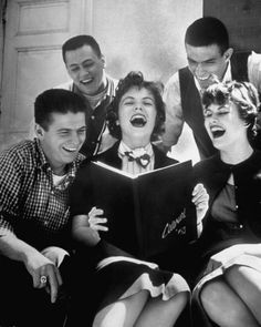 Teens, 1958  During a break between classes, high School Seniors roar with laughter as they look over pictures in the newly published yearbook. Life.