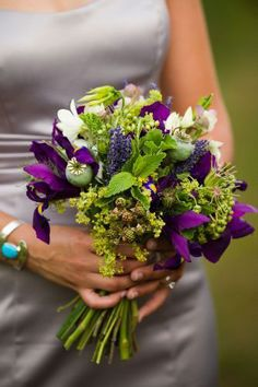Hand-tied bridal bouquet with iris, blackberries, herbs, seedpods, dendrobium orchids and alchemilla