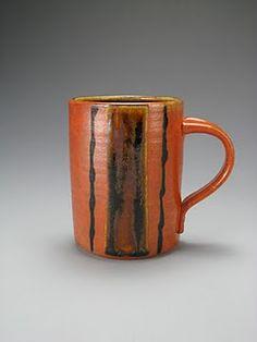 Cone 10 soda/salt fired mug with flashing slip, temmoku glaze panel and black decorating slip.