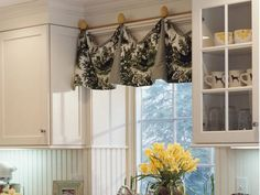 Suspended above the kitchen sink by painted, wooden eggs, a valance in chicken toile fabric adds country style to this traditional kitchen.