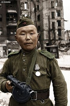 Red Army soldier from the farthest steppes of the Soviet Union poses triumphant in the devastated streets of Berlin, May 1945.