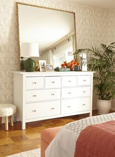 Chic white dresser styled with an oversized bamboo framed mirror