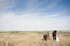 Western newlyweds in hay field with horse