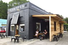 canteen.  existing building painted black with exposed wood slat siding