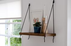 simple wooden shelf hung with ropes