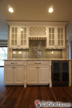 Bright and elegant home bar designed with Jupiter Maple Bright White wall and base cabinets, post legs, a wine rack, a stemware rack, and a variety of decorative moldings. #homebar