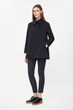 This lightweight coat is a flared A-line shape with a wide rounded collar and hidden press stud fastening along the front. Made from lightly textured fabric, it has 7/8 sleeves and two front welt pockets.