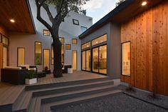 Una casa moderna en forma de U diseñada en torno a árboles