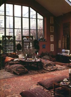 bohemian apartment: wall-to-wall oriental rugs, plush pillows as seats, low tables, candles, earthy colors, many unique patterns, large window, and look at the ceramic, textile & art decoration, and look at the scene outside!