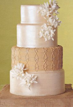 Four-tier wedding cake. Love the shimmery tiers, flowers, and pattern on the second to largest tier.