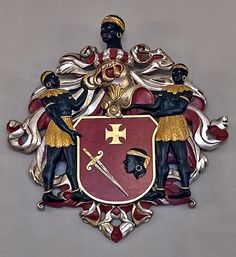 The Coat of Arms of the dignified and historic House Of Blackheads in Riga, Latvia. The Brotherhood of Blackheads was founded in 1399 for German merchants and ship owners, and establishing a prestigious headquarter too in Latvia. It was destroyed during WW2 by the Nazis and Soviets, but was rebuilt in 2001. St. Maurice, the European Patron Saint is the one depicted on the design.