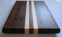Esta tabla de cortar es construida para durar. Está hecho con maderas de nogal, arce y Drago y sus medidas son 17 1/2 W x 10 1/2 H x 1 1/4 de