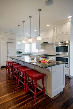 Wite kitchen with red saddle bar stools. Kitchen with mini pendant lights over white kitchen island with black countertops