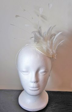This is a pretty handmade 1920s/Great Gatsby style bridal fascinator, with a gorgeous large ivory and grey feather. It is decorated with beautiful hand stitched cream pearls and swarovski crystal detailing and comes on an cream sinamay base and headband.  The fascinator is presented in a lovely gold fascinator box, which is ideal for storage and transportation!  This item would be perfect for a wedding, the races or a party!  There is currently 1 item in stock, which can be shipped within 1…