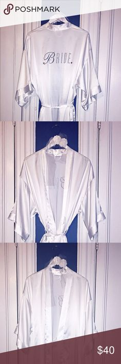 """Victoria Secret Satin Bride Robe with Hanger! From the Victoria's Secret """"I do"""" Collection, this sexy satin white """"Bride"""" robe is a MUST for the big day! """"Bride"""" detailing on the back is a clean combination of flat glitter lettering and rhinestones. Thin satin inserts and a beautiful satin outer rope are perfect to keep everything in place. Hang this up with the *INCLUDED* white wooden hanger with organza flower detailing! Worn once. Victoria's Secret Intimates & Sleepwear Robes"""